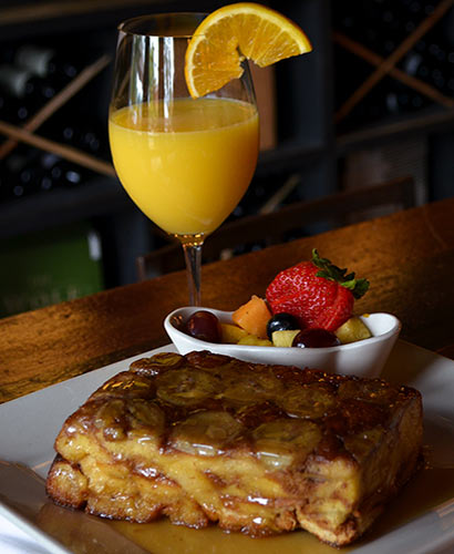 Bananas Foster brunch dish with mixed fruit side dish in front of orange juice in wine glass.